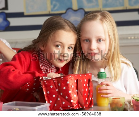 Primary School Pupils Enjoying Packed Lunch In Classroom - stock photo