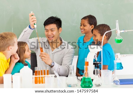 primary school science teacher demonstrating science experiment - stock photo