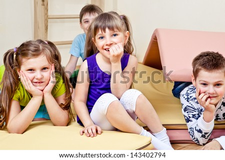Primary school students sitting on tumbling mats - stock photo