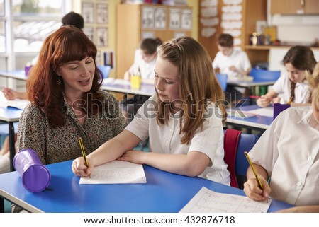 Primary school teacher helping a girl writing at her desk - stock photo
