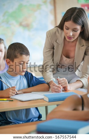 Primary school teacher helping a student in class. - stock photo