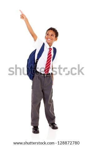 primary schoolboy pointing at empty copyspace isolated on white