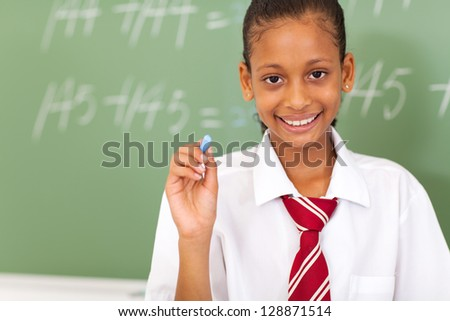 primary schoolgirl holding chalk in front of chalkboard - stock photo