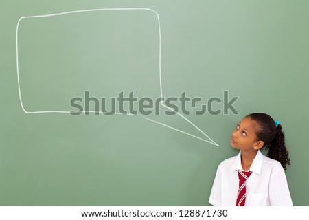 primary schoolgirl looking at chat box drawn on blackboard