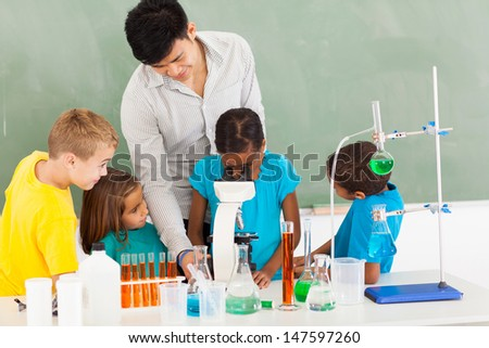 primary teacher and students in science class with young girl using microscope - stock photo