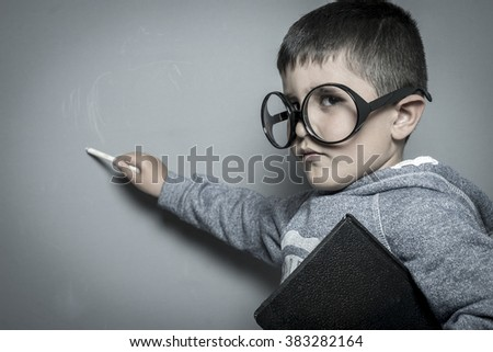 primary, young student writing on a blackboard school with a book in hand and big glasses - stock photo