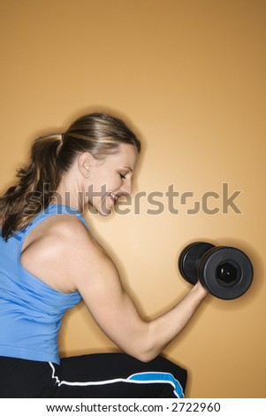Prime adult female Caucasian lifting hand weights. - stock photo