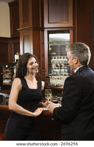 Prime adult Hispanic female and Caucasian prime adult male standing at bar talking. - stock photo