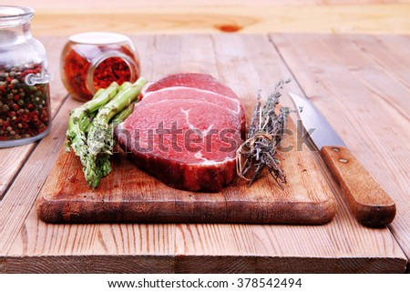 prime fillet meat : dry raw beef on cutting board with asparagus , thyme bundle , color peppercorn mix and red paprika powder mixed with dry spices over wooden table ready to cooking - stock photo