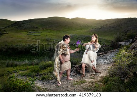 Primitive caveman dressed in animal skin giving flowers to happy cave woman in the mountains
