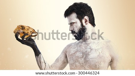 primitive man looking a rabbit skull over ocher background - stock photo