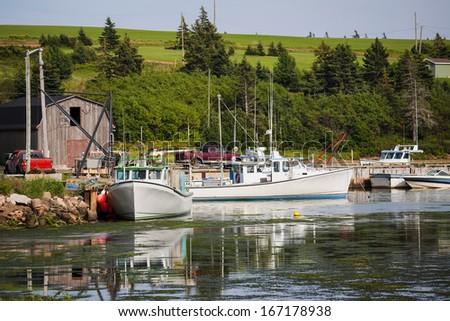 Prince Edward Island fishing boats tied up at the wharf. - stock photo