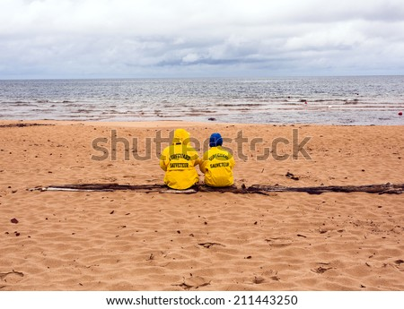 Prince Edward Island National Park Greenwich, Canada at Beach on Rainy Day Two Lifeguards in Yellow Raincoats - stock photo