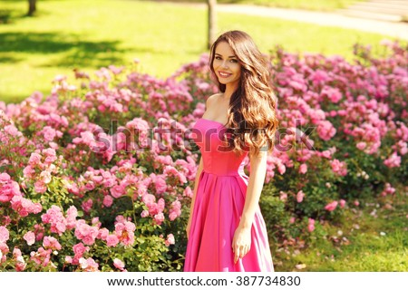 Princess. Young beautiful pretty woman posing in long evening luxury dress against bushes with pink roses on a sunny summer day. Vogue style fashion sensual portrait