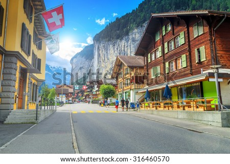 Principal street of Lauterbrunnen with shops, hotels, terraces, swiss flags and stunning Staubbach waterfall in background, Bernese Oberland, Switzerland, Europe - stock photo