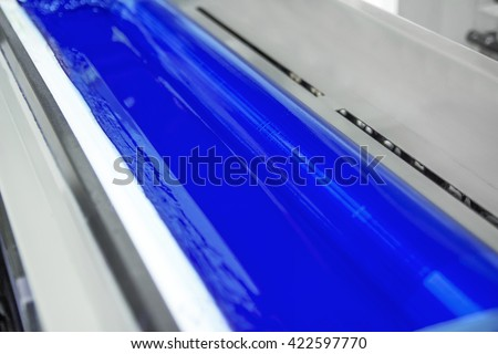 print machine printing press rollers, cyan, blue color drum, dramatic light - stock photo