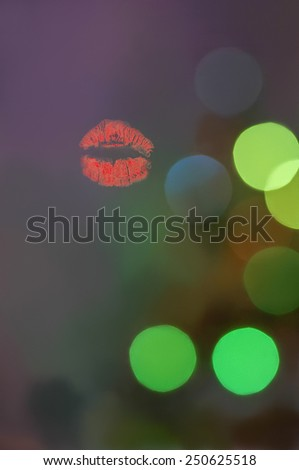 Print of red lips on evening bokeh blurred background, focus on lips - stock photo
