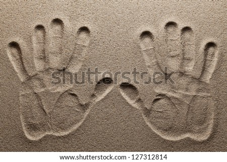 Print of two hands on sand. - stock photo