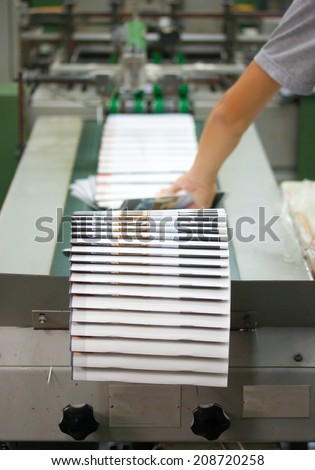 Print shop - Finishing line. Post press finishing line machine: cutting, trimming, paperback. - stock photo