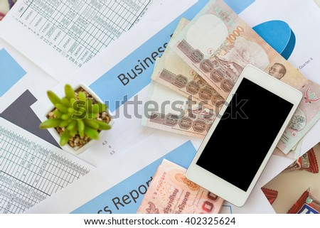 Printed Business Annual Report in Charts ,thai banknote, calculator and smartphone .business concept. - stock photo