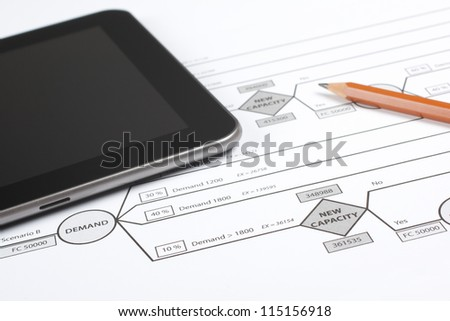 Printed decision tree (new factory capacity expansion), digital tablet and pencil. Workplace of manager making decision about strategy. - stock photo