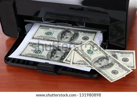 Printer printing fake dollar bills on wooden background - stock photo