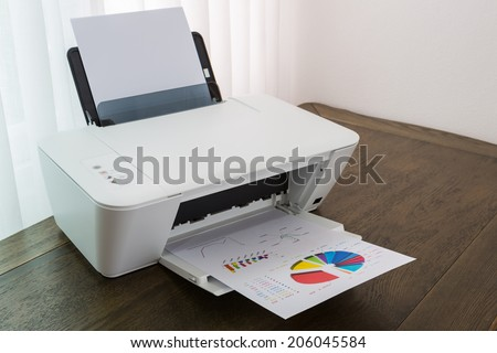 Printer with financial documents on a wood table - stock photo