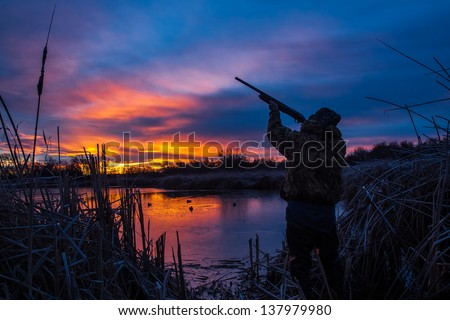 Prior to a Christmas duck hunt; I went out to a pond in Pendleton, Oregon during the blue hour (about 25 minutes before sunrise) and set up this self portrait of myself.  Title: Christmas Duck Hunt - stock photo