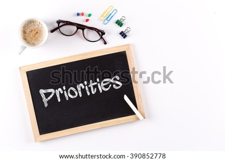Priorities word on chalkboard with coffee cup and eyeglasses, view from above - stock photo