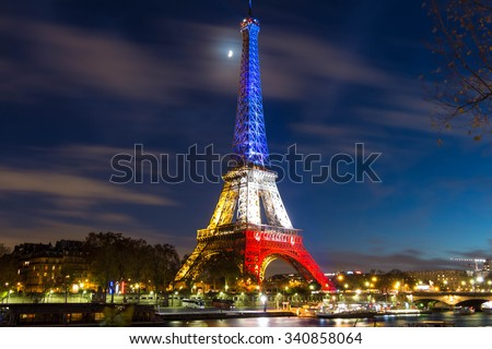 Pris, France-November 18, 2015 : The Eiffel tower lit up with the colors Of the French national flag (Blue, White and Red)to honor the victims of November 13 Friday's terrorist attacks in Paris. - stock photo