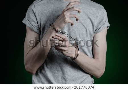 Prison and convicted topic: man with handcuffs on his hands in a gray T-shirt and blue jeans on a dark green background in the studio, put handcuffs on the drug dealer - stock photo