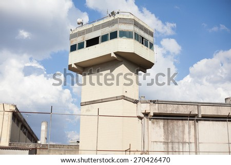 Prison tower and walls surrounded by gate - stock photo