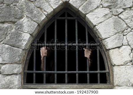 prisoner behind bars of a dark prison  - stock photo