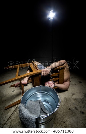 Prisoner being punished with cruel interrogation technique of waterboarding.  The man is restrained and tortured. - stock photo