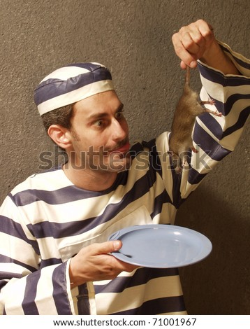 prisoner eating a rat on a prison cell. - stock photo