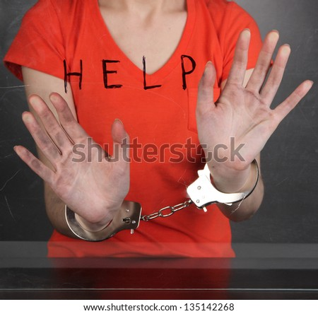 Prisoner in handcuffs behind glass in soundproof room - stock photo