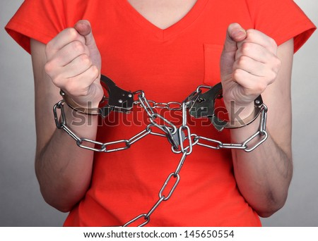 Prisoner in handcuffs on grey background - stock photo