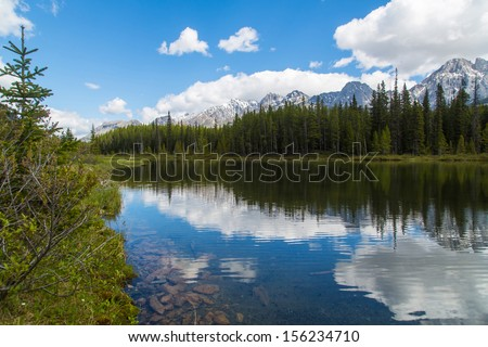 Pristine Lake in Canadian Rockies with mountains on background - stock photo