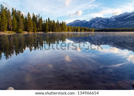 Pristine  lake surrounded by pine forest in Rockies. Early morning.
