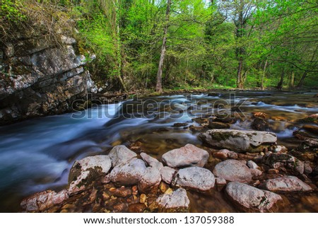 Pristine silky stream and waterfalls in limestone mountains in spring