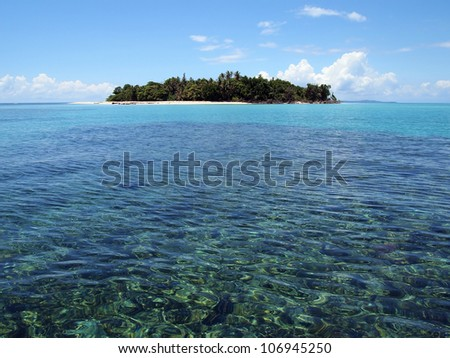 Pristine tropical island at the horizon with turquoise water in foreground - stock photo
