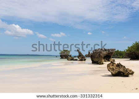 Pristine white tropical beach with rocks, blue sea and lush vegetation on the African Island of Misali, Pemba, Zanzibar.