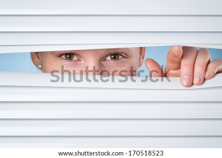 Privacy or spying concept - a young woman opening closed shutters and peeking through them.