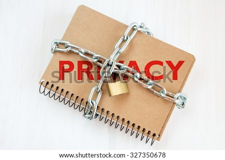 Privacy protection concept, notepad with chain and padlock - stock photo