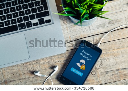 Privacy settings on smart phone screen. Detail of workplace. - stock photo