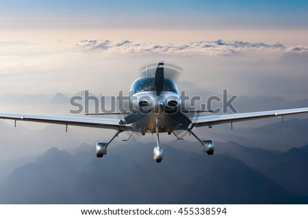 Privat light airplane or aircraft fly on mountain background. VIP travel concept - stock photo