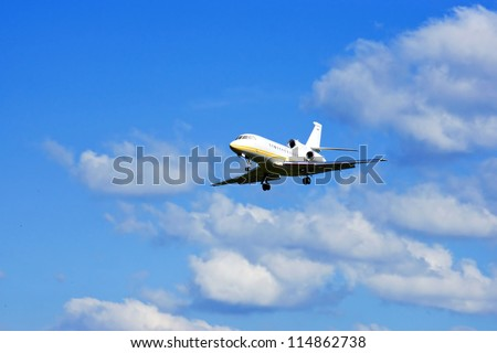 Private business jet airplane flying against blue sky with clouds background