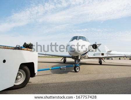 Private business jet being towed by ground crew