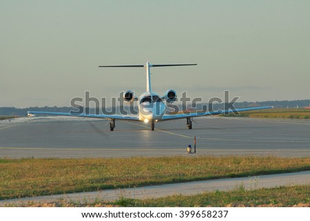 Private business jet taxiing along the runway to take off or after landing on sunset