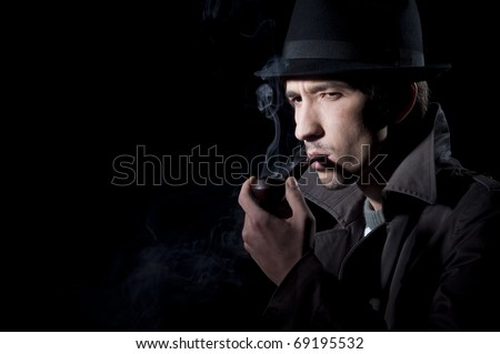 private detective smoking a pipe, isolated on a black background - stock photo